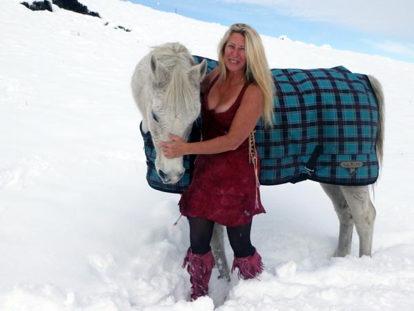 Wearing a red braintan buckskin dress with a white horse.